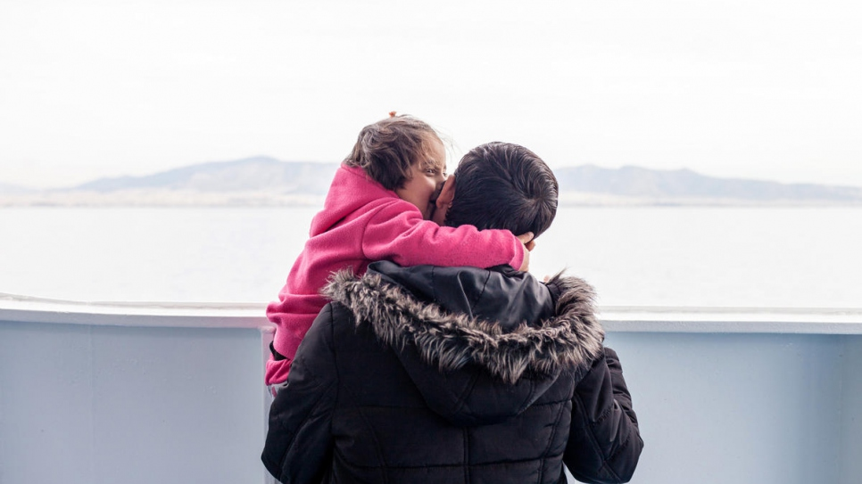 Mohamad Alhajer with his four-year-old daughter Maria on the ferry Nissos Chios taking them from the island of Samos to start a new life in mainland Greece.