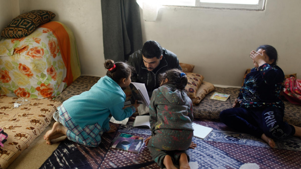 After his shift at the factory, 33-year-old Syrian refugee Mohammed Jamal Kabour helps his girls with their homework.