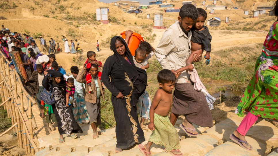 Mohammad Harez and Momena Begum trek with their children to a new shelter on high ground in Kutupalong refugee settlement, Bangladesh.