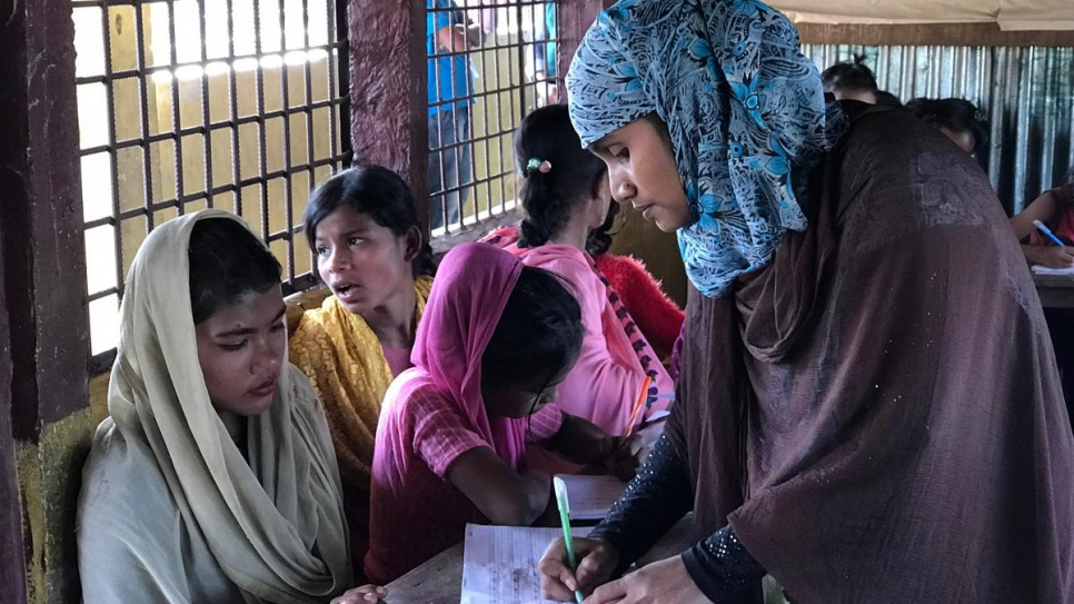 Rohingya refugee teacher Alinesa, 32 (one name only) marks the work of pupil, newly arrived refugee, Rosina Akhter, 12.