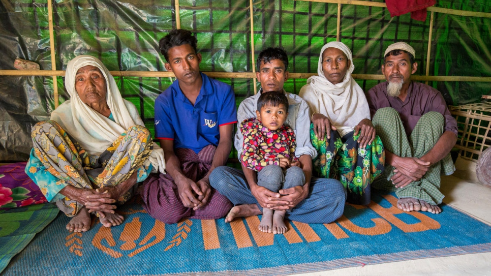 Gul Zahar, 90, Mohammad Siddiq, 25, Mohammad Ayub, 31, Kismat Ara, 3, Ayesha Begum, 40, and Oli Ahmed, 53, sit in their one-room shelter in Bangladesh.