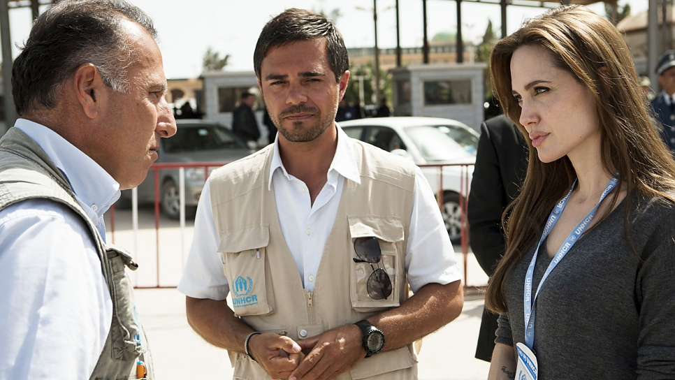 UNHCR Special Envoy Angelina Jolie speaks with UNHCR staff members Ayman Gharaibeh and Patrick Mansour at Ras Djir, on the Tunisia-Libya border, in February 2011.