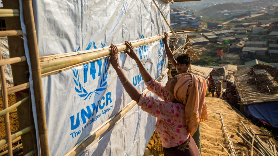 Rohingya refugees reinforce their shelters with materials supplied by UNHCR at the Kutupalong refugee settlement.
