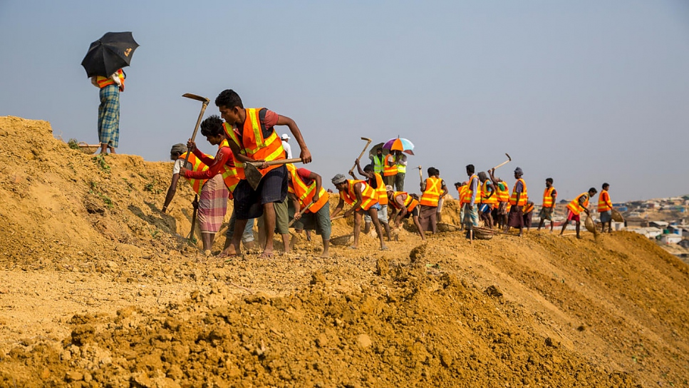 Labourers work to level a slope at a site west of the current boundary of Kutupalong refugee settlement.