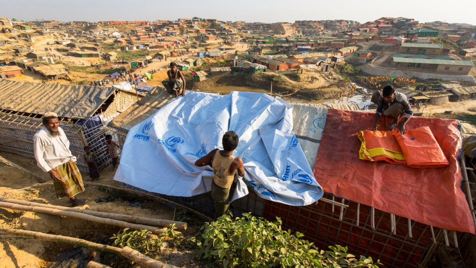 A refugee reinforces a shelter with a tarpaulin supplied by UNHCR at the Kutupalong refugee settlement, Bangladesh.