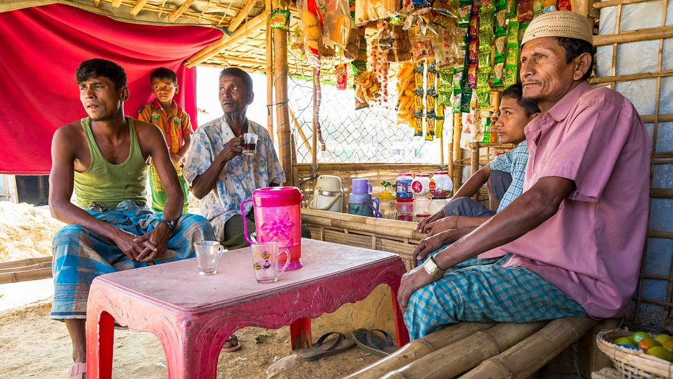 Mohammad Islam (centre) takes tea at a stall run by Kabir Ahmed (right) and his son Nur Mohammad (left) in Kutupalong Refugee Settlement, Bangladesh.