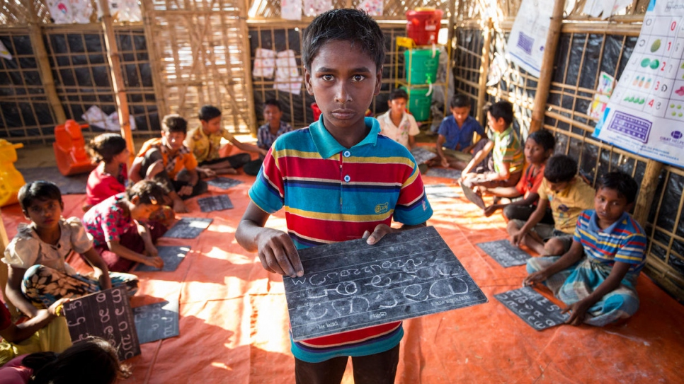 Ayatullah, 11, writes on a chalkboard in a classroom at Kutupalong Refugee Settlement. He recently fell ill with suspected diptheria and was successfully treated at a nearby medical centre.