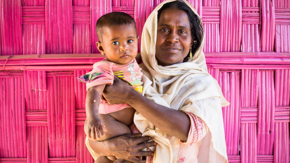 Single mother Laila Begum, 25, holds her 10-month old son, Josna Bibi, outside a sewing workshop run by the Bangladesh Rural Advancement Committee in Kutupalong refugee settlement.