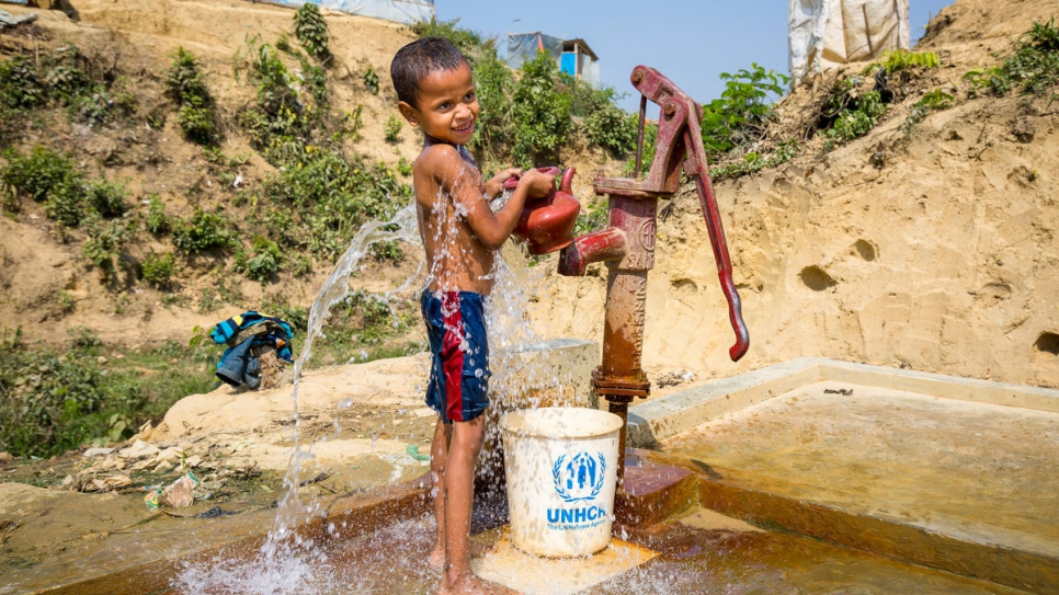 A young boy fills a bucket and kettle at a standpipe in Kutupalong refugee settlement.