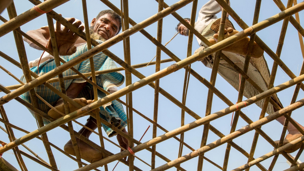 Refugee Mohammad Ishaq (left) strengthens the roof of his shelter with bamboo provided by UNHCR to residents of Kutupalong refugee settlement, Bangladesh, ahead of the monsoon.