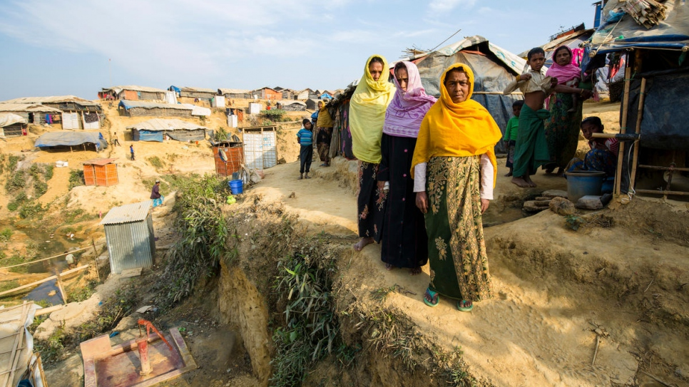 Siraj Begum, 38, yellow scarf, Mariam Khatun, 60, violet scarf, and Nur Nahar, 45, orange scarf, stand outside their shelter in Kutupalong refugee settlement, Bangladesh. Their home is on a steep hillside deemed at risk of collapse in the monsoon rains.
