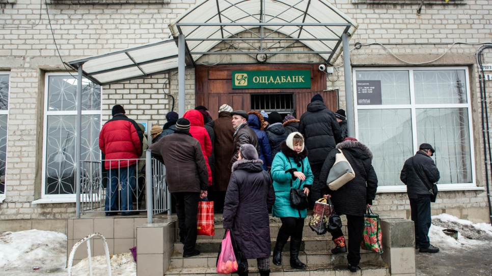 Pensioners wait to withdraw their pensions from the state bank in Volnovakha.
