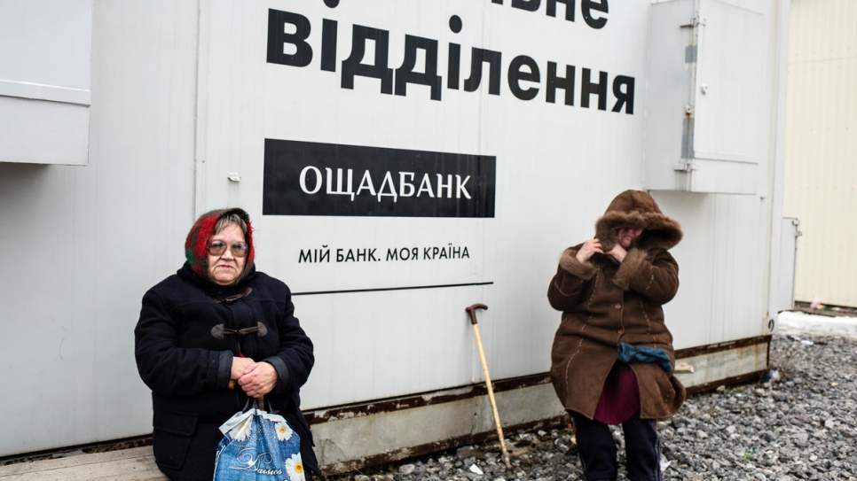 Nelia (left) spent hours waiting beside this mobile bank at Novotroitske checkpoint.