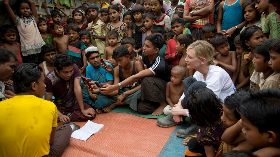 Cate Blanchett watches a performance by Rohingya refugee Mohammed Sayidul Islam (left, purple t-shirt) and other musicians at Kutupalong refugee settlement.