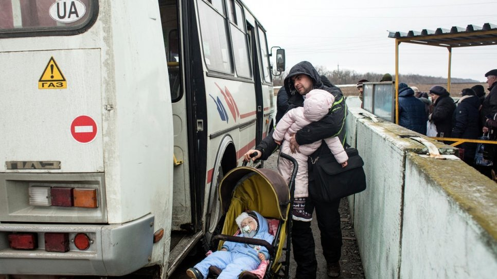 A man boards a bus with two children at Mariinka checkpoint.