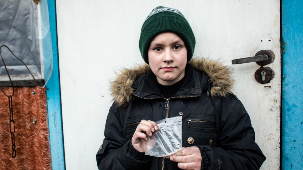 Misha holds a piece of shrapnel that was removed from his head.