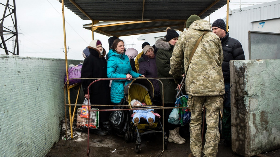 People wait to cross Mariinka checkpoint.