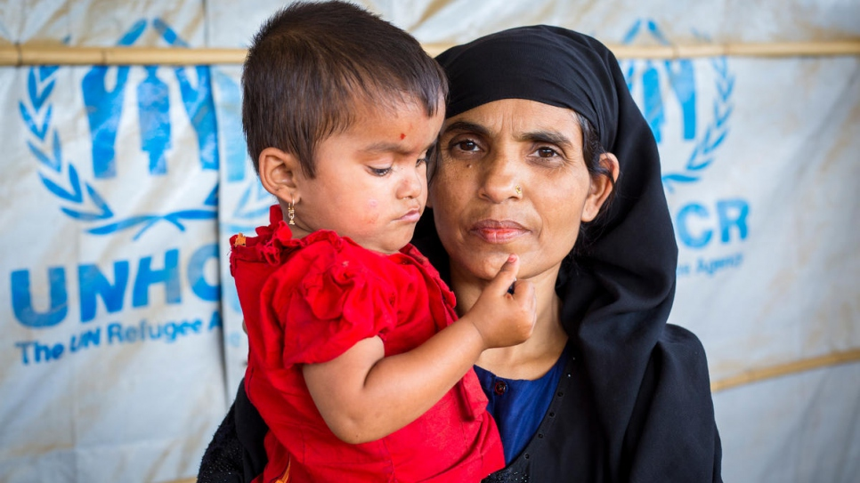 Khatemunnesa, 40, holds her daughter at a UN Refugee Agency Information Point in Kutupalong refugee settlement, Bangladesh.