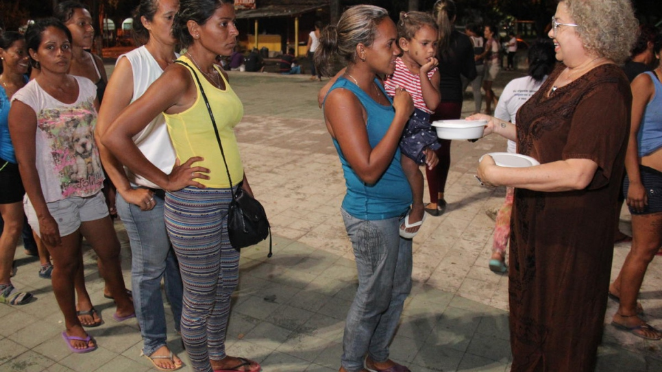 Ana Lucíola Franco (right) gives food donations to Venezuelans camped out in Simon Bolivar Square, Boa Vista, Brazil.