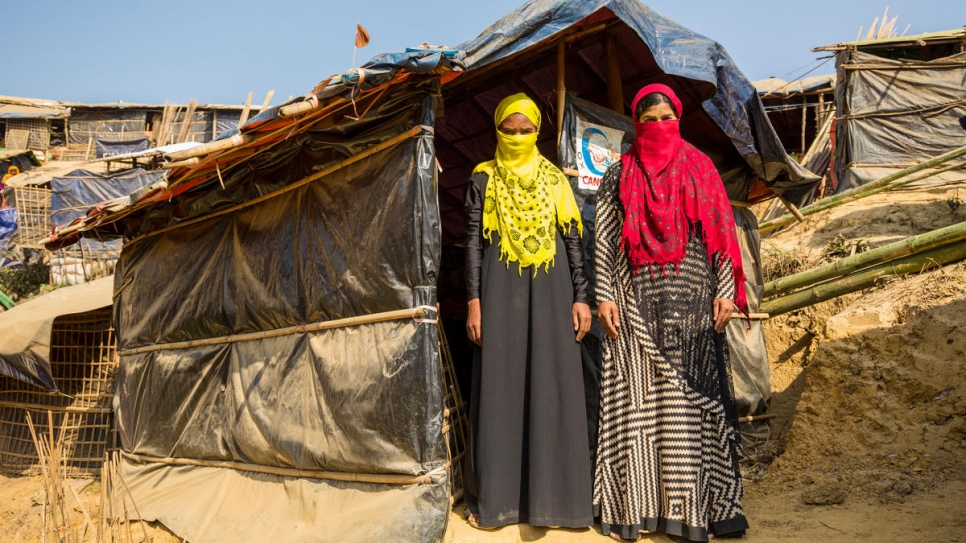 Mabia, left and  Shamshidah, right, stand outside their borrowed shelter at Kutupalong refugee settlement in Bangladesh.