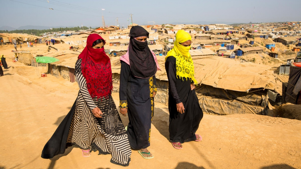 Shamshidah, left, and Mabia, far right, walk to their shelter in Kutupalong refugee settlement, accompanied by refugee widow they met at the UNHCR information point.