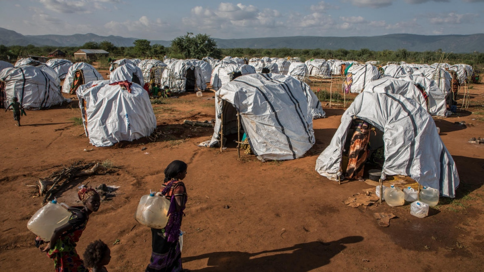 Women carry water to their temporary shelter at a refugee camp in Sololo, Marsabit County in  Kenya.