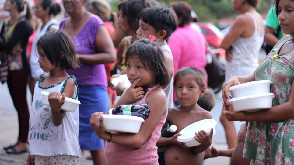 Venezuelans living in Simon Bolivar Square in Boa Vista line up for food provided by local community members.