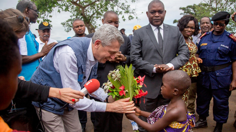 UN Refugees Chief Filippo Grandi is greeted by a young Burundi refugee girl at Mulongwe refugee camp  in South Kivu, DRC.