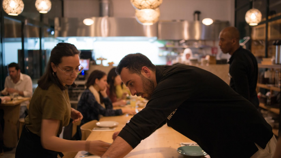 Syrian waiter Rafat Dabah sets the table for service at Mezze, Lisbon's Syrian restaurant. He has joined his mother and two sisters on the staff of Mezze.