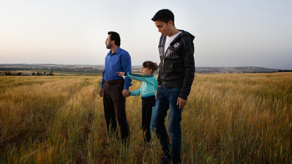 Syrian refugee Hamed Mifleh (left), 47, and his children Ahmad, 21, and Bara'a, 7, walk in a field near their home in Madaba, Jordan.