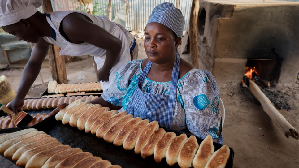 Mama Safi Kisasa, a refugee and small business owner, makes fresh bread with family members.