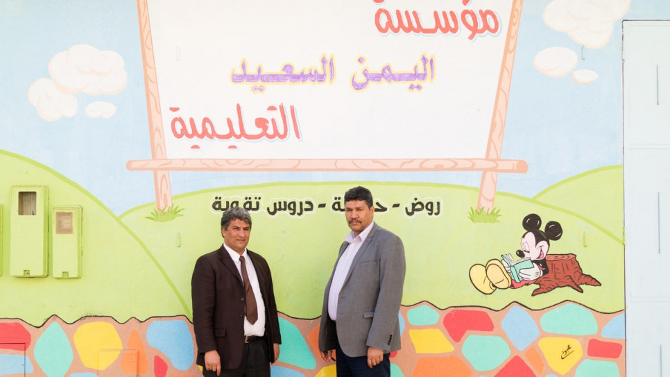 Abdullah (right) stands outside the school building with a member of staff.