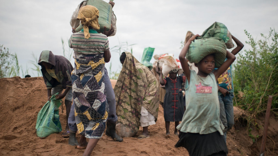 After packing the sand into 25-kilogram sacks, displaced women and children carry it to construction sites in Kalemie, the capital of DR Congo's Tanganyika Province.