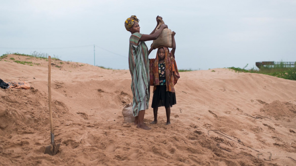 A Congolese mother and child who have been displaced by conflict work an early-morning shift packing and transporting sand from Lake Tanganyika to local construction sites.
