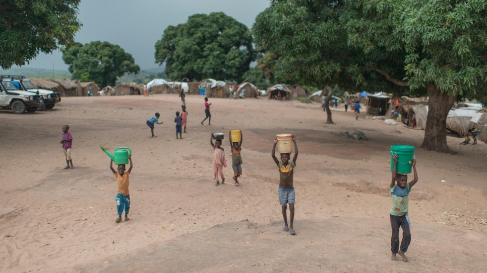 Congolese children carry water back to their shelters at Kaseke, a site for internally displaced people in war-torn Tanganyika Province.