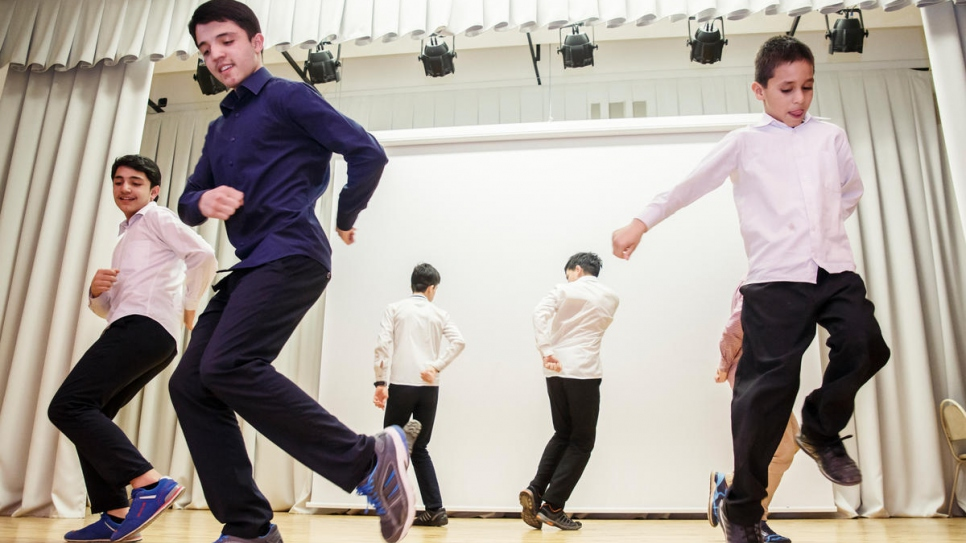 Six Afghan boys learn a traditional dance at Evrika community center.