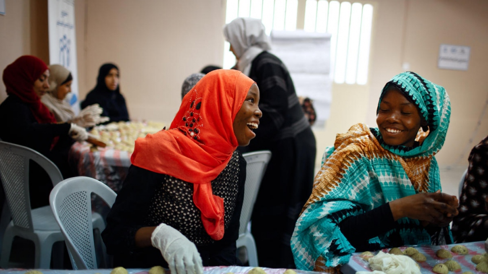 Sudanese refugee sisters Zainab Abdallah (left in red) and Nuha (right) make an Arabic sweet for Eid at Princess Basma Centre for Social Development in Amman, Jordan.