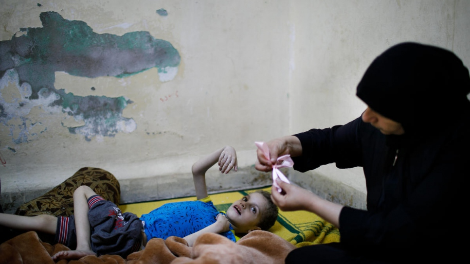 Syrian refugee Ghania Hamweh plays with her son Abdul Hadi at their home in Al Hussain refugee urban camp in Jordan. Ghania has three children who suffer from brain paralysis and epilepsy. She received two packages of the sweets.