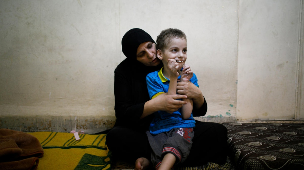 Syrian refugee Ghania Hamweh, from Homs, plays with her son Abdul Hadi at their home in Al Hussain refugee urban camp in Jordan.  She received sweets made by refugees and their Jordanian hosts in Amman, Jordan.