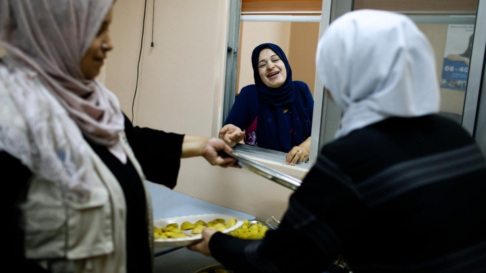 Najwa Al Bedour (centre), Director of Princess Basma Centre for Social Development, interacts with refugee and Jordanian cooks preparing ma'moul, in Amman, Jordan.