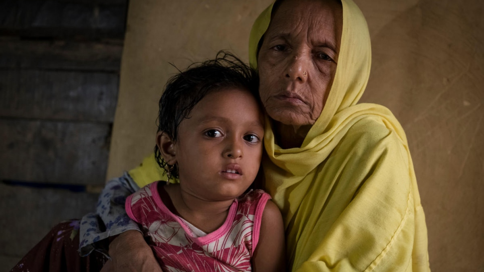 Rohingya refugee Mutaybatu, 55, holds her adopted granddaughter at a shelter in southeast Bangladesh. She fled Myanmar in 2017.