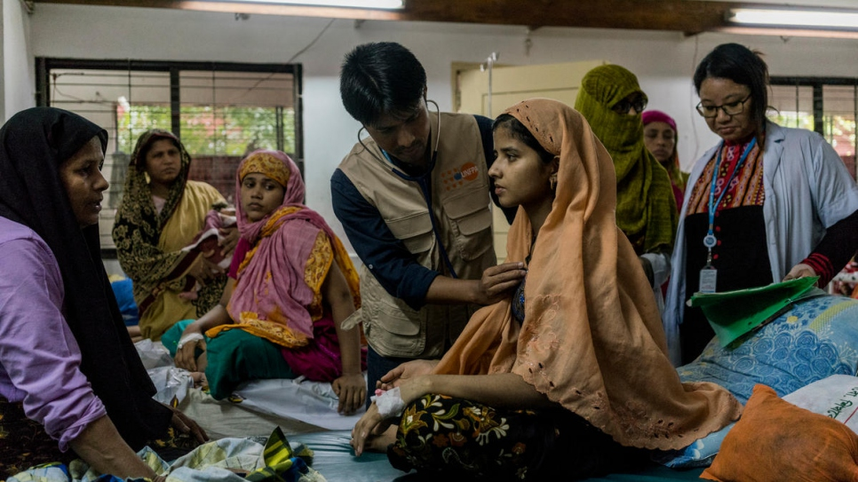 Sailesh Rajbanshi, an obstetrician gynaecologist working for the UN Population Fund, checks on Milishi, 18, a Rohingya refugee in a mixed ward with Bangladeshi patients, at Sadar Hospital in Cox's Bazar, Bangladesh.