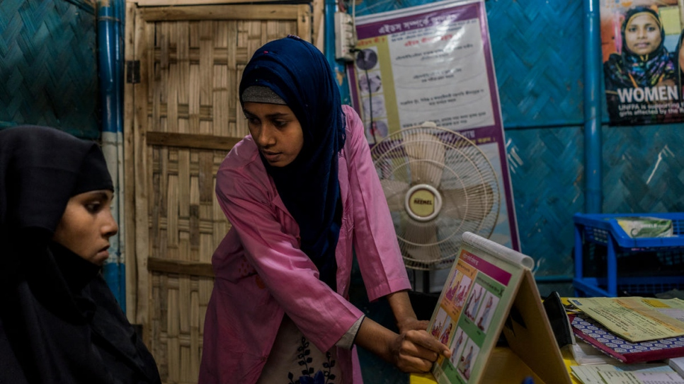 Midwife Shirin Akter, 21, teaches Romida Begue, 25, a pregnant Rohingya mother of two, about her health during pregnancy at a primary health care facility funded by UNHCR and UNFPA in Bangladesh.