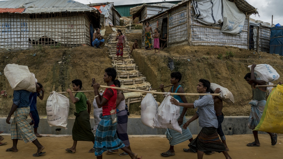 Rohingya refugees, who were living in tents at risk of landslides, carry their belongings as they are relocated to the new Camp 4 Extension, in Kutupalong refugee settlement in Bangladesh.