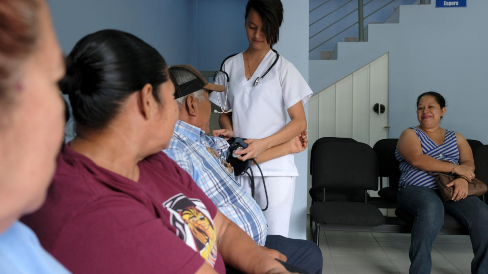A medic checks a patient's blood pressure at the UNHCR-backed Holy Trinity Comprehensive Support Centre in Chamalecón, San Pedro Sula, Honduras.