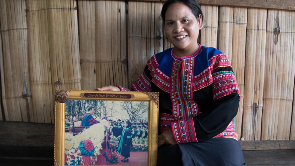 Natee, a formerly stateless woman from the Lahu hill tribe, shows a photograph of her university graduation