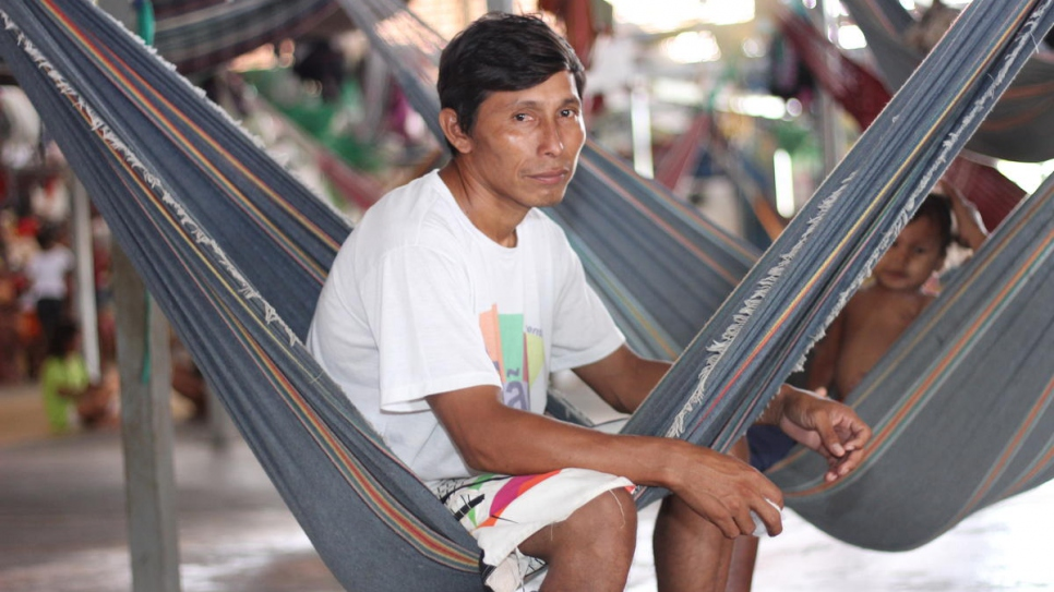Warao community leader Eligio Tejerina, 33, sits in a hammock next to his children at Pintolandia Shelter in Boa Vista, northern Brazil.