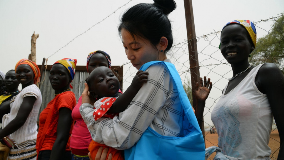 UNHCR communications officer Eujin Byun holds a refugee baby at a camp in South Sudan.