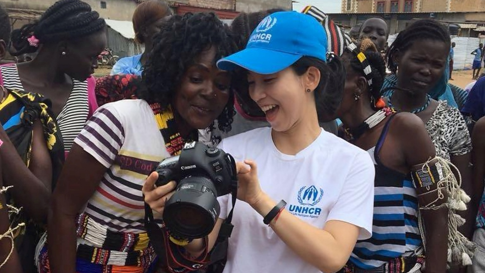 UNHCR communications officer Eujin Byun shows pictures to women at a refugee camp in South Sudan.