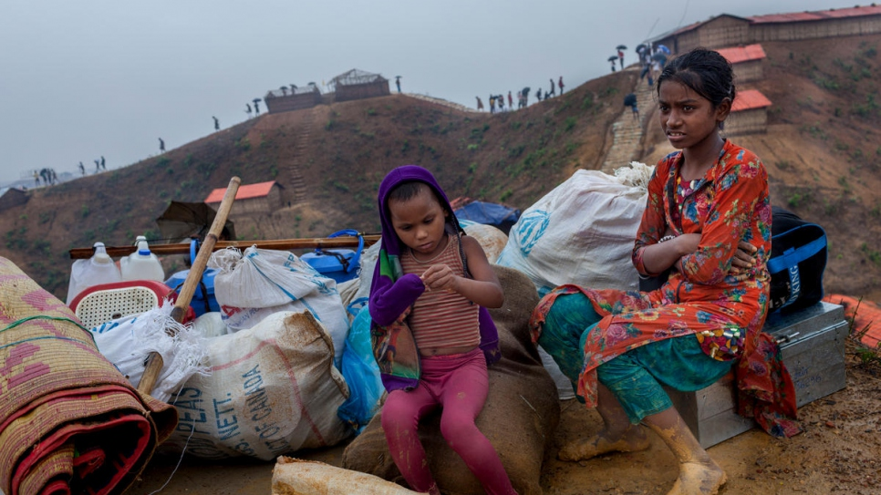 Rohingya refugees Bibi, 4, and Jannatul, 11, sit with their belongings as they wait to move into a new shelter at Camp 4, Kutupalong. Their family's previous home was destroyed by a landslide.